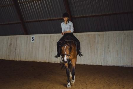 Girl in outfit riding horse