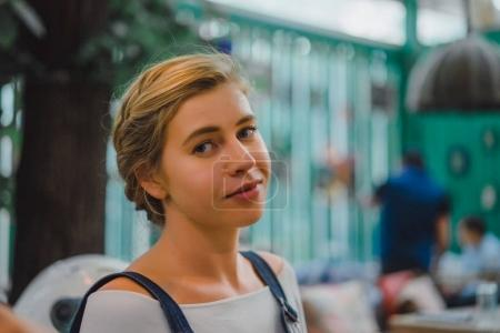 happy young blonde woman at outdoor cafe