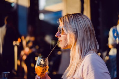 Photo pour Belle femme blonde buvant un cocktail d'alcool en plein air café d'été - image libre de droit