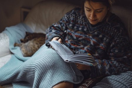 Photo pour Une jeune femme sous un plaid avec chat passe un temps confortable à lire un livre intéressant . - image libre de droit