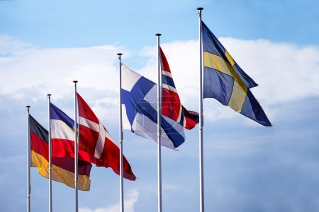 flags of the nordic european countries  in the wind against the blue sky