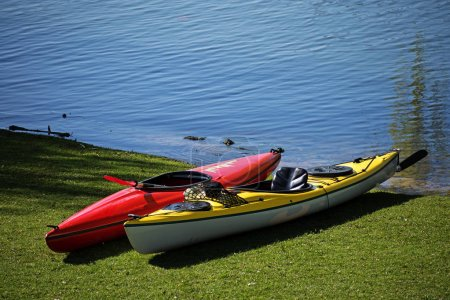 Two kayaks lie in the lawn on the shore of a lake, ready for leisure activity