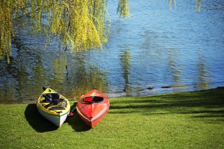 Two kayaks lie under a tree in the grass on the shore of a lake, ready for leisure activity