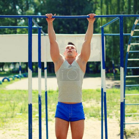 Sport, street workout concept - athlete doing pull ups on the ho