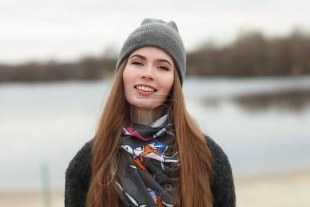 Full length lifestyle portrait of young and pretty adult woman with gorgeous long hair posing in city park with shallow depth of field in grey coat, hat, scarf