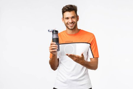 Fitness instructor holding water bottle and pointing at it as recommend drink after workout. Handsome mascular man share his knowledge about diet and healthy lifestyle, standing white background