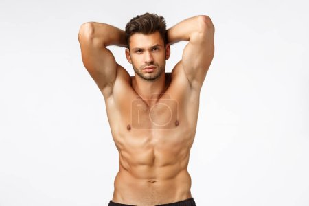 Photo for Bodybuilder goined movember. Sexy handsome tanned caucasian man with bristle, standing naked torso, proudly showing six-pack abdominal abs, hold hands behind head, have perfect body, white background. - Royalty Free Image
