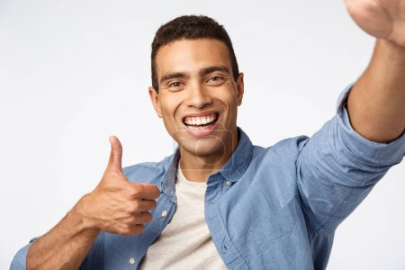 Photo for Cheerful supportive boyfriend encourage girlfriend as talking video-call, holding device with stretched hand, touch camera, make thumbs-up in approval or like, smiling satisfied, white background. - Royalty Free Image