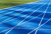 blue tartan track in a track and field stadium
