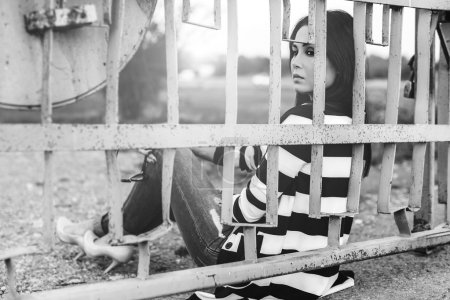 young woman sitting behind fence