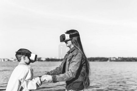 Sister with  brother playing in VR glasses