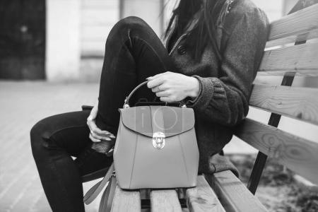 Woman sitting on the bench with bag in hands, black and white