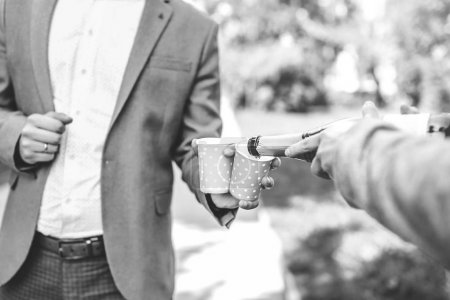 groom holding paper cups