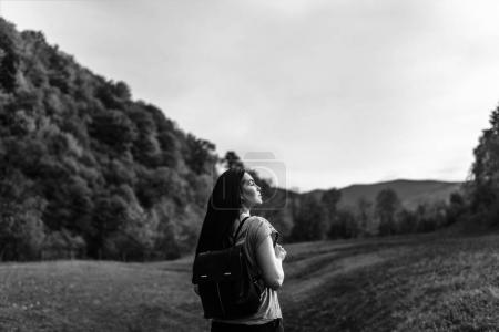 Travel girl with backpack traveling in the mountains