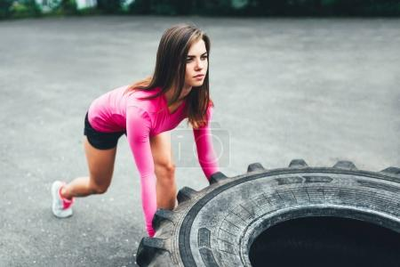 girl lifting huge tire