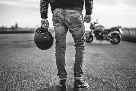 homme tenant le casque de moto