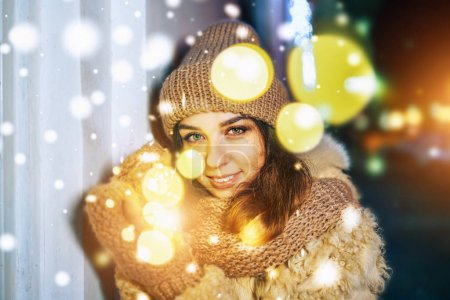 Outdoor portrait of smiling girl in knitted hat holding Christmas lights