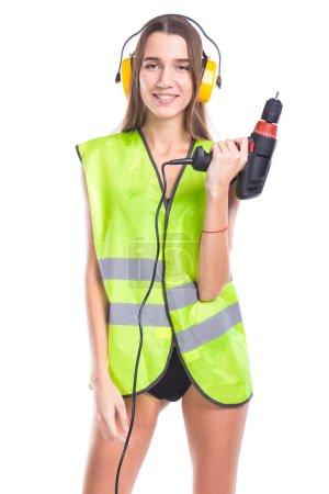 Photo pour Photo verticale, isolé sur blanc, caucasienne Jolie brunette jeune sexy femme en tenue verte builder, cache-oreilles jaunes et bikini noir, tournevis de tenir d'une main, regardez caméra, souriant - image libre de droit