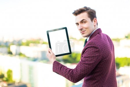 Businessman in suit on the roof with tablet
