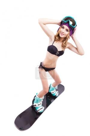 young pretty woman in bikini on snowboard