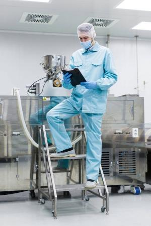scientist with tablet by metal tank