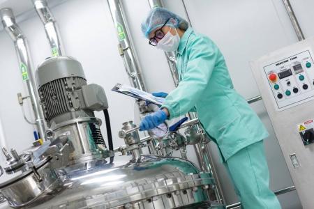 scientist standing near tank in factory