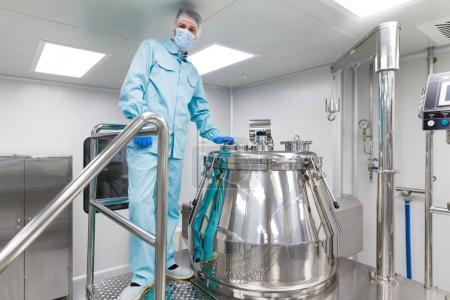 scientist stand near big metal barrel