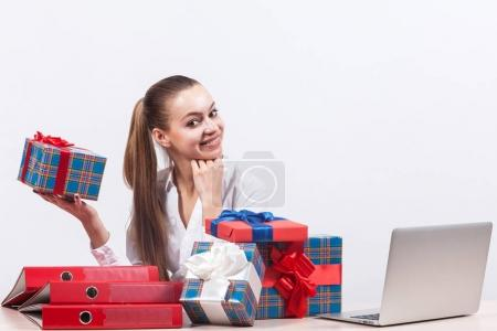 Businesswoman with gifts in office by laptop