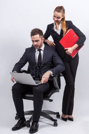Young businesspeople with a laptop and office folders