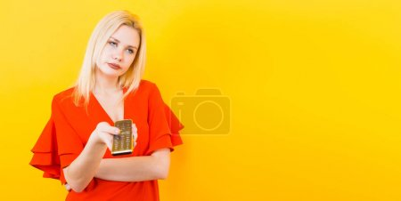 Beautiful young woman in red dress posing with remote control on yellow background