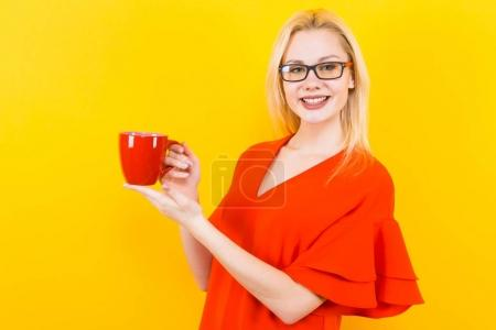 Beautiful young woman in red dress posing with cup on yellow background