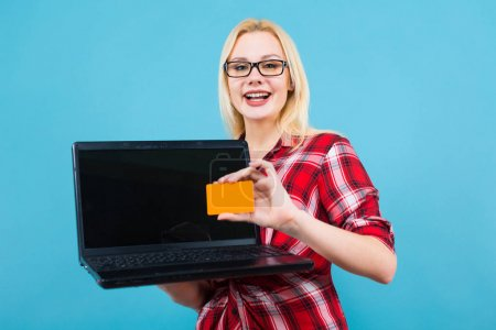 Studio portrait of beautiful young woman holding modern laptop and blank orange business card on blue background
