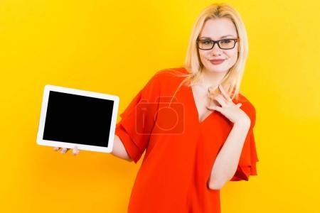 Photo for Beautiful young woman in red dress posing with tablet PC on yellow background - Royalty Free Image