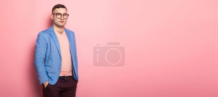 Handsome young man in blue jacket holding hands in pockets on pink background