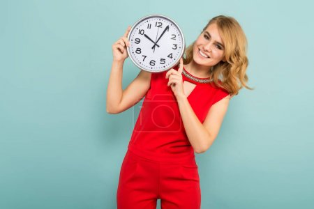 Young blond woman  holding clock against blue studio background