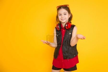 Photo pour Jolie petite fille brune avec un moderne casque rouge gesticulant - image libre de droit