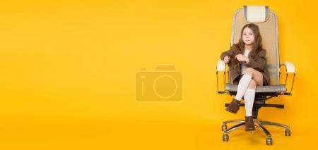Cute little brunette girl sitting in modern office chair on yellow background