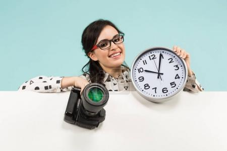 Young brunette woman holding professional photo camera and wall clock
