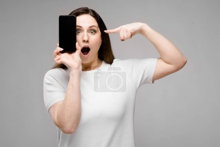 Photo for Beautiful curvy brunette woman with long luxurious hair in simple white t-shirt showing different expressions on grey wall in studio while posing with her smartphone. - Royalty Free Image