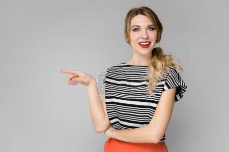 attraktive junge kaukasische blonde Frau in lässigem Outfit mit verschiedenen Ausdrucksformen an grauer Wand im Studio.