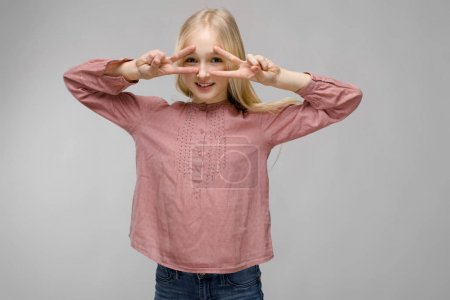 Pretty caucasian blonde teenage girl in checkered shirt and glasses showing different emotional expressions on grey wall in studio.
