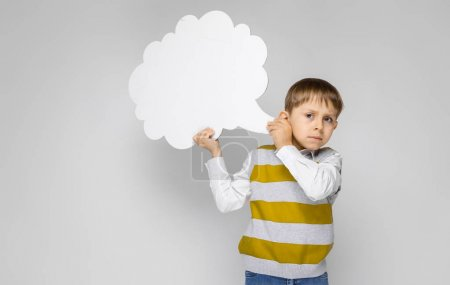 Photo for Portrait of adorable little boy holding speech cloud on grey background - Royalty Free Image