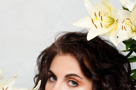 Photo for People, emotions, natural, beauty, flowers and lifestyle concept - Beauty girl takes beautiful flowers in her hands. Blowing flower. Hairstyle with flowers. Summer fairy portrait. Long permed hair. - Royalty Free Image
