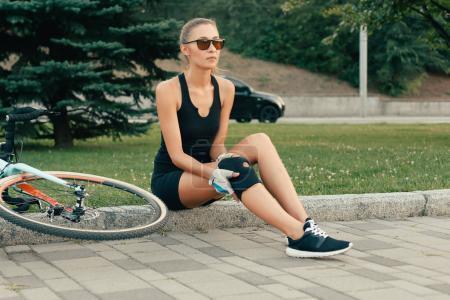 Foto de Gente, deporte, 4k, salud y estilo de vida concepto - forma chica tocando su rodilla lesionada después de un día de accidente de moto. Muchacha de protección de la rodilla para downhill bicicleta en cámara lenta. chica tiene un dolor en su rodilla - Imagen libre de derechos