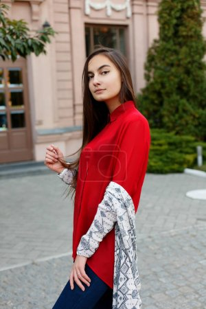 Photo for Charming young woman with a magnificent brunette hair, big eyes, gorgeous red lipstick and stylish look. Attractive young lady is rushing in the city-center, she turns to camera and smiles. - Royalty Free Image