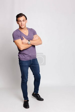Photo for Emotion, advertisement and people concept - Handsome young man on grey background looking at camera. Portrait of laughing young man in pockets leaning against grey wall. Happy guy smiling. - Royalty Free Image