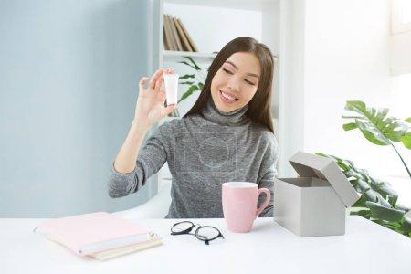 Photo pour La blogueuse beauté montre un nouveau produit de beauté à la caméra. Elle enregistre une nouvelle vidéo pour sa chaîne. Le produit est la crème pour les mains. Elle le regarde et sourit - image libre de droit