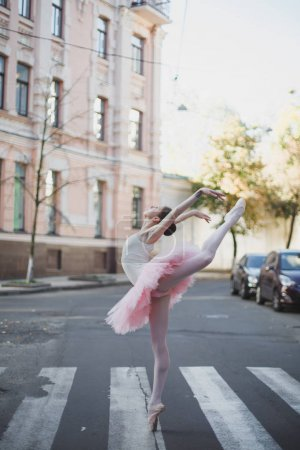 Photo for Young and graceful ballerina performing on the city street - Royalty Free Image
