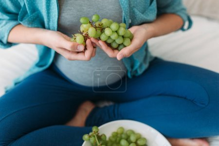 pregnant woman eating grapes