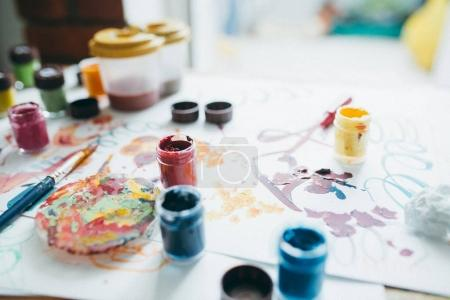 Photo for Messy table of artist with paints, brush and paper - Royalty Free Image